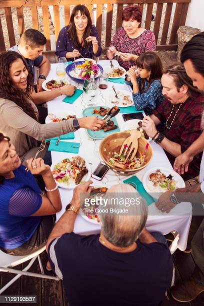 family laughing together during outdoor celebration dinner - medium group of people stock pictures, royalty-free photos & images