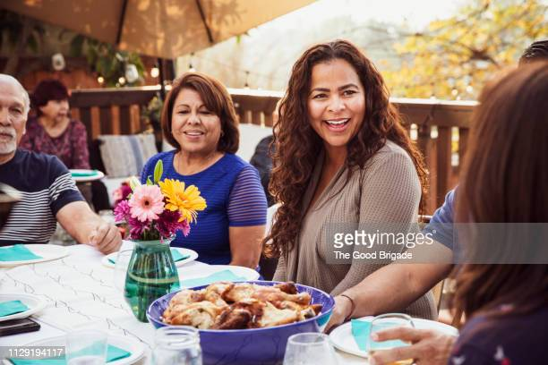 family laughing together during outdoor dinner party - latino américain photos et images de collection
