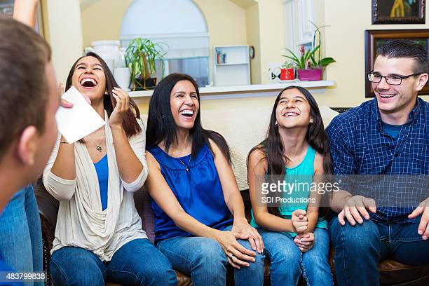 Family laughing while playing game together in living room