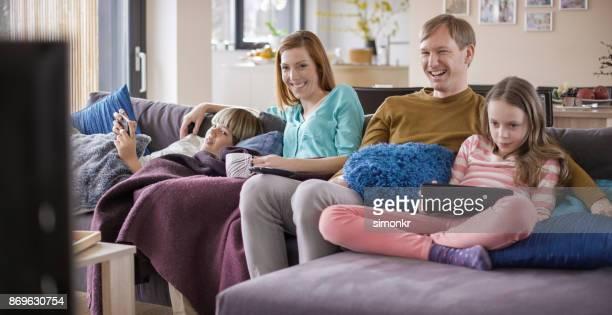 Famille de rire en regardant la télévision sur le canapé