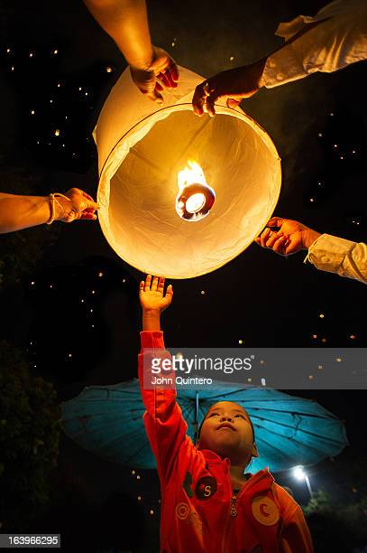 CONTENT] Family launching a lantern into the sky on the third day of Loy Krathong Festival in Chiang Mai Thailand By releasing the lanterns to the...