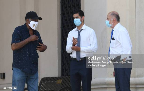 Family lawyers Michael and Luis Carrillo speak with the father, left, of Anthony McClain in front of the Pasadena Police Dept. After viewing the...