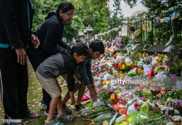 A family lay flowers by the wall of the Botanic Gardens on March 17 2019 in Christchurch New Zealand 50 people are confirmed dead with 36 injured...