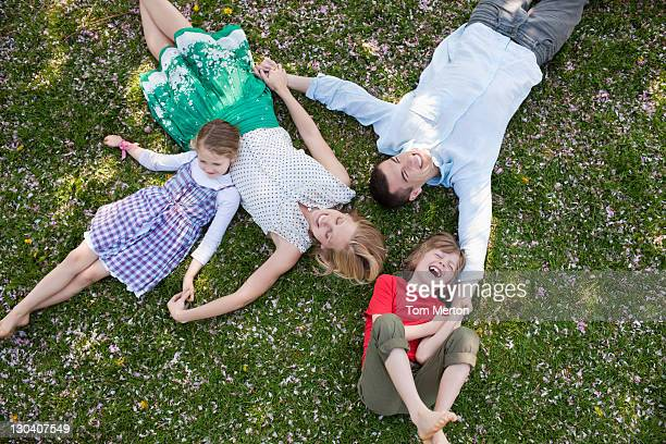 Family laying in grass together