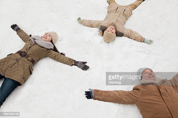 Family laying in snow making snow angels