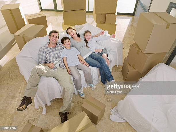 Family laying on sofa surrounded by cardboard boxes
