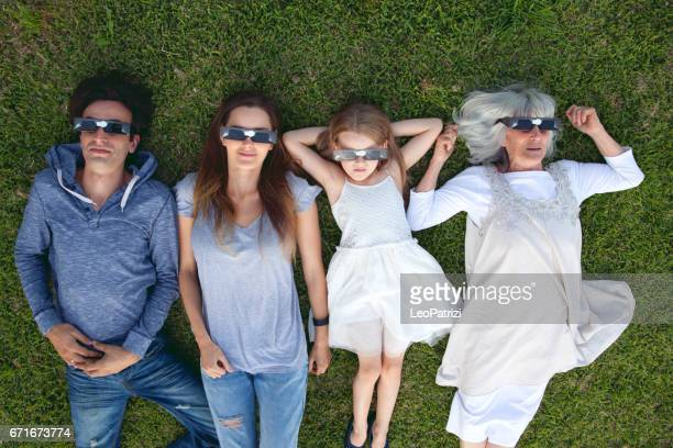 Family laying on the grass looking at Solar Eclipse