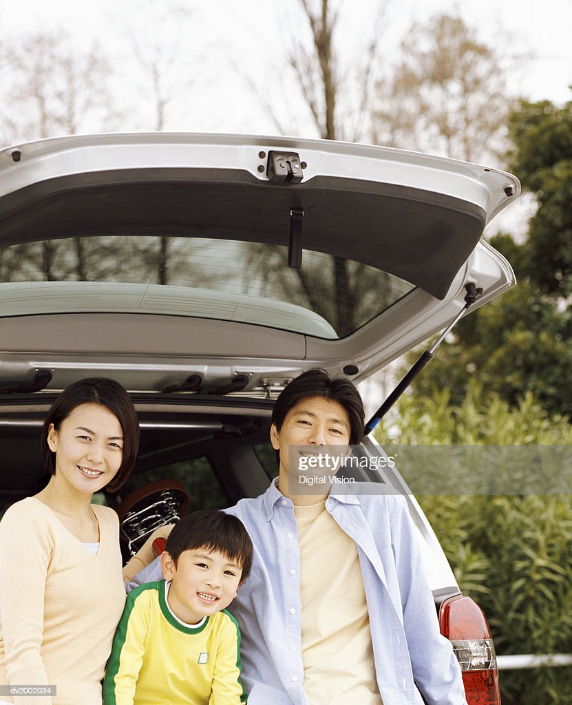 Family Leaning Against the Back of a Car : Stock Photo