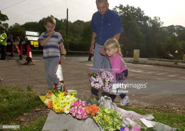 A family leave flowers in tribute to Milly Dowler at the police road block near Yateley Heath Minley in Hampshire where what are believed to be...