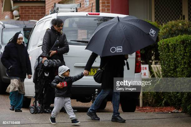 A family leaves an apartment complex in Sproule Street Lakemba on July 31 2017 in Sydney Australia Counter terrorism police raided four houses across...