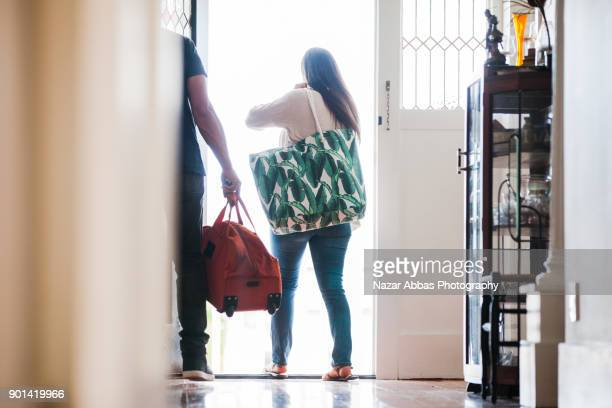 Family leaving home with bags in hand.