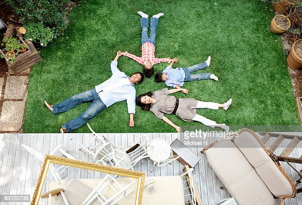 Family lie down on lawn in garden