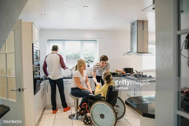 family life in the kitchen with disabled daughter - epilepsy stock pictures, royalty-free photos & images