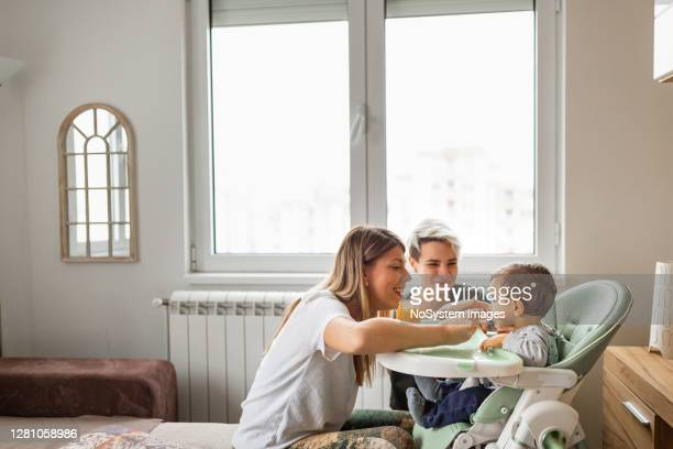 family life. lesbian couple with baby at home. - parent stock pictures, royalty-free photos & images