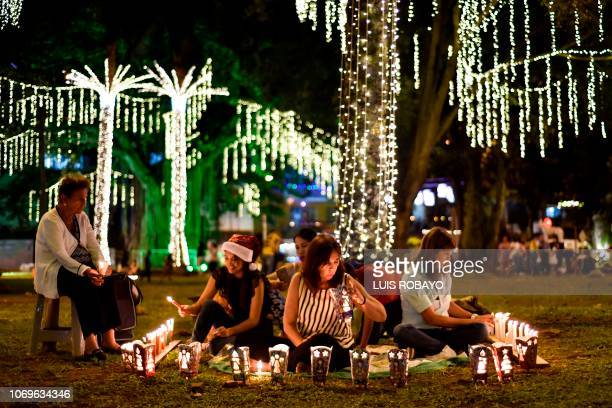 A family light candles during the Day of the Little Candles in Cali Colombia on December 7 2018 The Day of the Little Candles is a traditional...