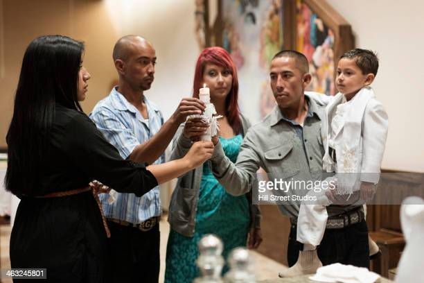 family lighting baptismal candle in church - catholic baptism stock pictures, royalty-free photos & images