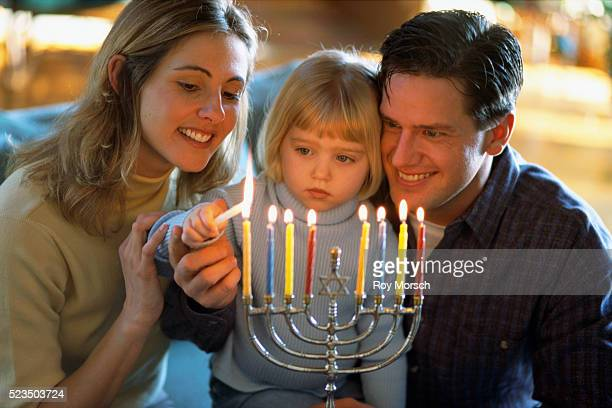 family lighting menorah - hanukkah stock pictures, royalty-free photos & images