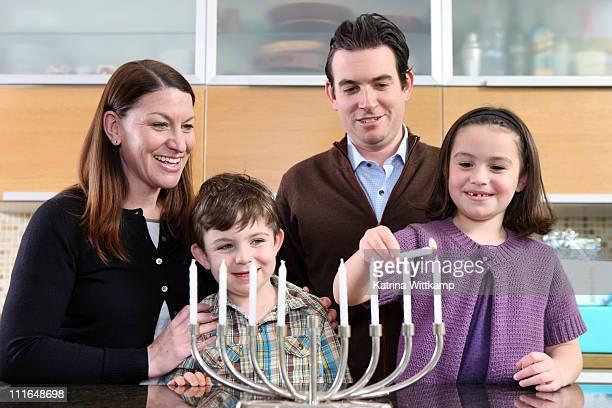 family lighting the menorah. - hanukkah stock photos and pictures