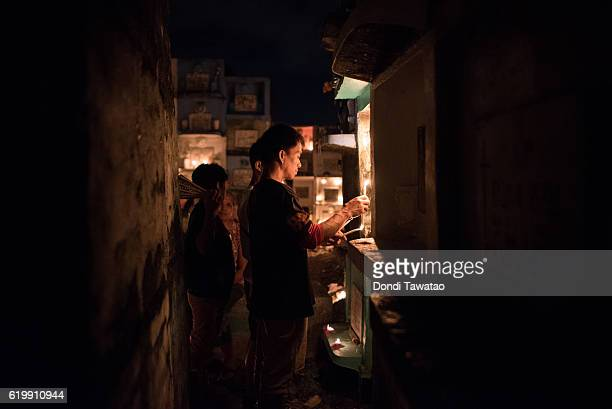 A family lights candles at a public cemetery on November 1 2016 in Manila Philippines Filipinos flock to cemeteries around the country to visit...
