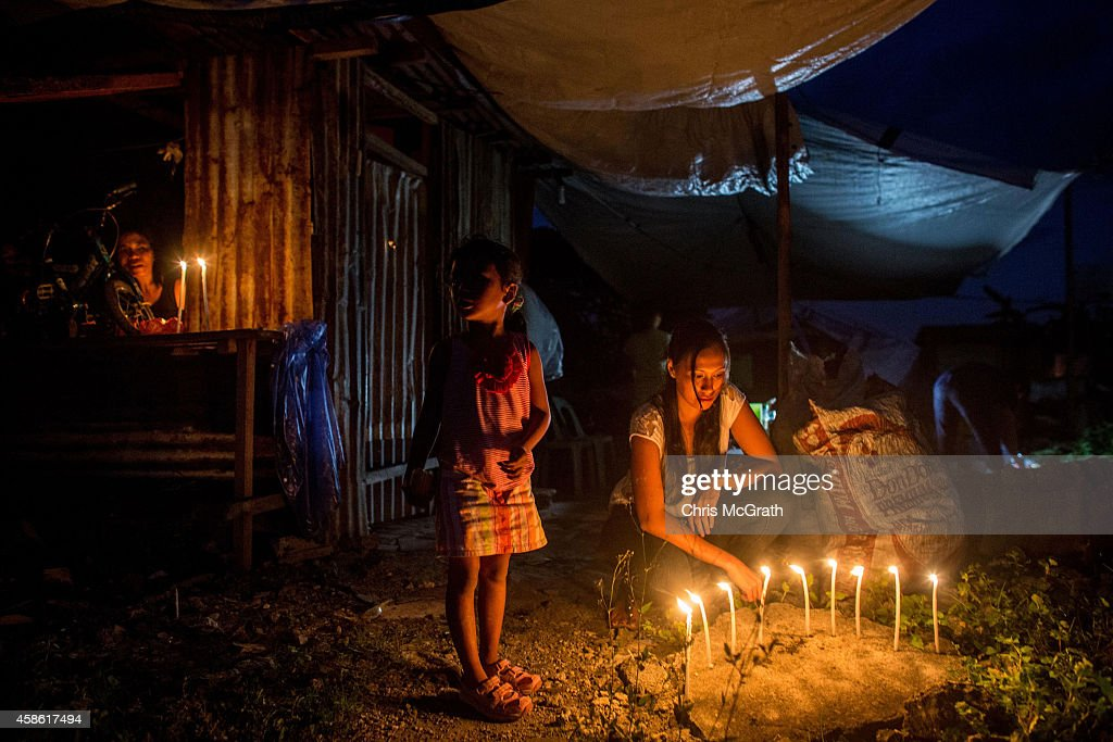 TACLOBAN, LEYTE, PHILIPPINES - NOVEMBER 08: A family lights candles outside their temporary home in San Jose during the candlelight memorial on November 8, 2014 in Tacloban, Leyte, Philippines. People lined the roads with candles all across Tacloban from the airport to downtown in remembrance of the victims of Typhoon Haiyan. Residents and typhoon survivors from across the central Philippines attended memorial services, candlelight vigils and visited mass graves honouring those who lost their lives one year ago when Typhoon Haiyan, the strongest typhoon ever to make landfall swept across the region, leaving more than 6000 dead and many more homeless.