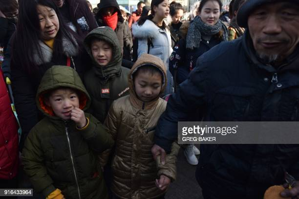 A family line up to enter a railway station in Beijing on February 10 as travellers depart the capital ahead of the Lunar New Year China is in the...