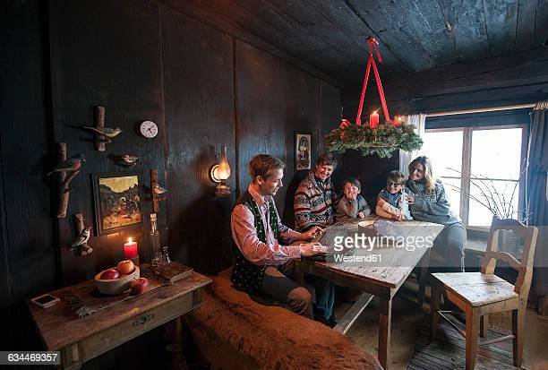 Family listening to a man playing zither in a farmhouse room at Advent