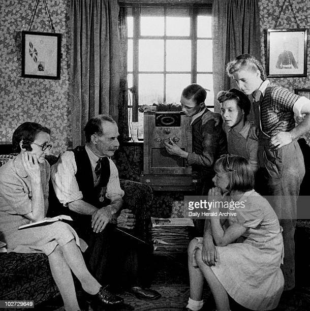 Family listening to a speech by Winston Churchill, 19 May 1945. Mr and Mrs Cooper and family tuning in their wireless to listen to a speech by Prime...