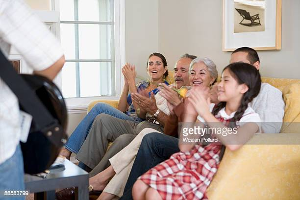 Family listening to boy play guitar in living room