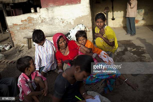 A family living in a slum gathers near a newly dug roadway April 22 2009 where agricultural areas they and members of twelve families have been...