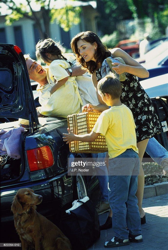 Family loading car with picnic hamper and luggage : Stock Photo