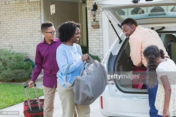 Famille de chargement les bagages dans la voiture va en vacances