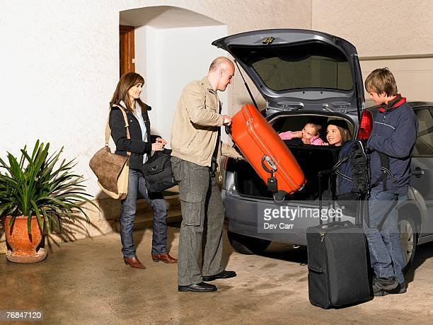 Family loading luggage into car on driveway