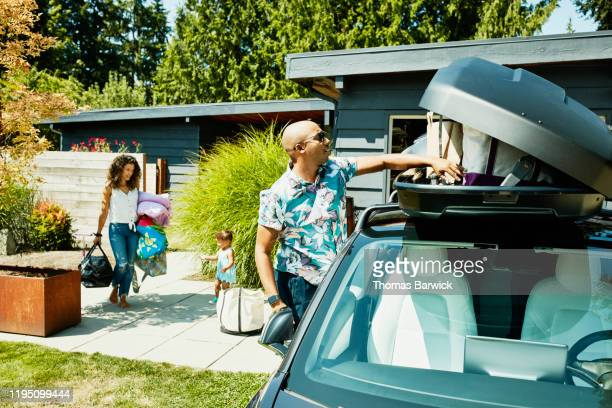 family loading luggage into car top box before road trip - road trip stock pictures, royalty-free photos & images