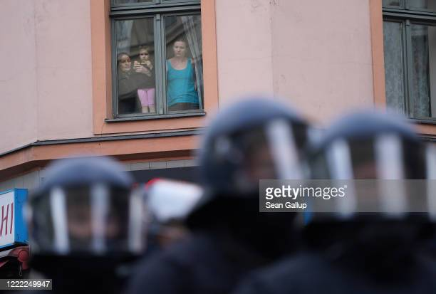 A family look down at riot police during scattered leftwing protests in Kreuzberg district on May Day during the novel coronavirus crisis on May 1...
