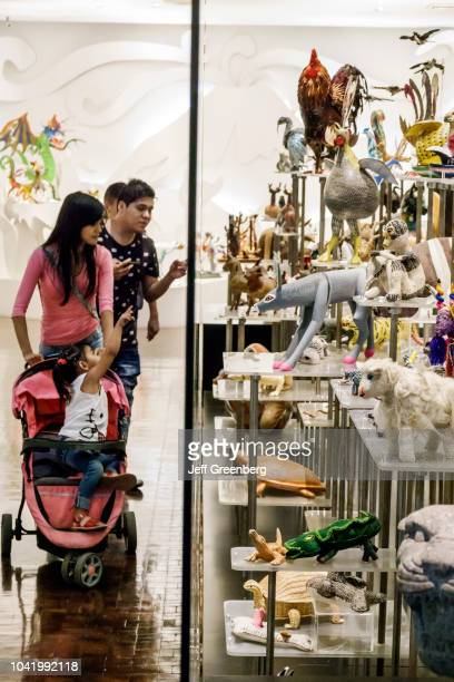 A family looking at animal figures on exhibit inside the Popular Art Museum in Mexico