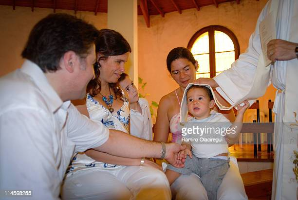 family looking at baby boy getting baptized - christening gown stock pictures, royalty-free photos & images
