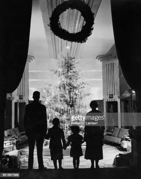 family looking at christmas tree in living room - noel noir et blanc photos et images de collection