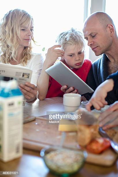 family looking at digital tablet at dining table - weekday stock pictures, royalty-free photos & images