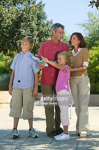 Family looking at guidebook and pointing