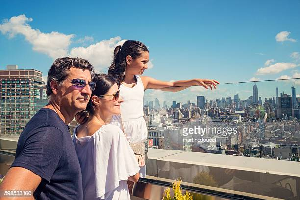 Family looking at New-York skyline on bright summer day.