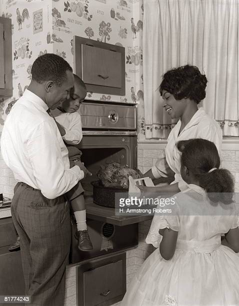 family looking at oven and roast turkey. - noel noir et blanc photos et images de collection