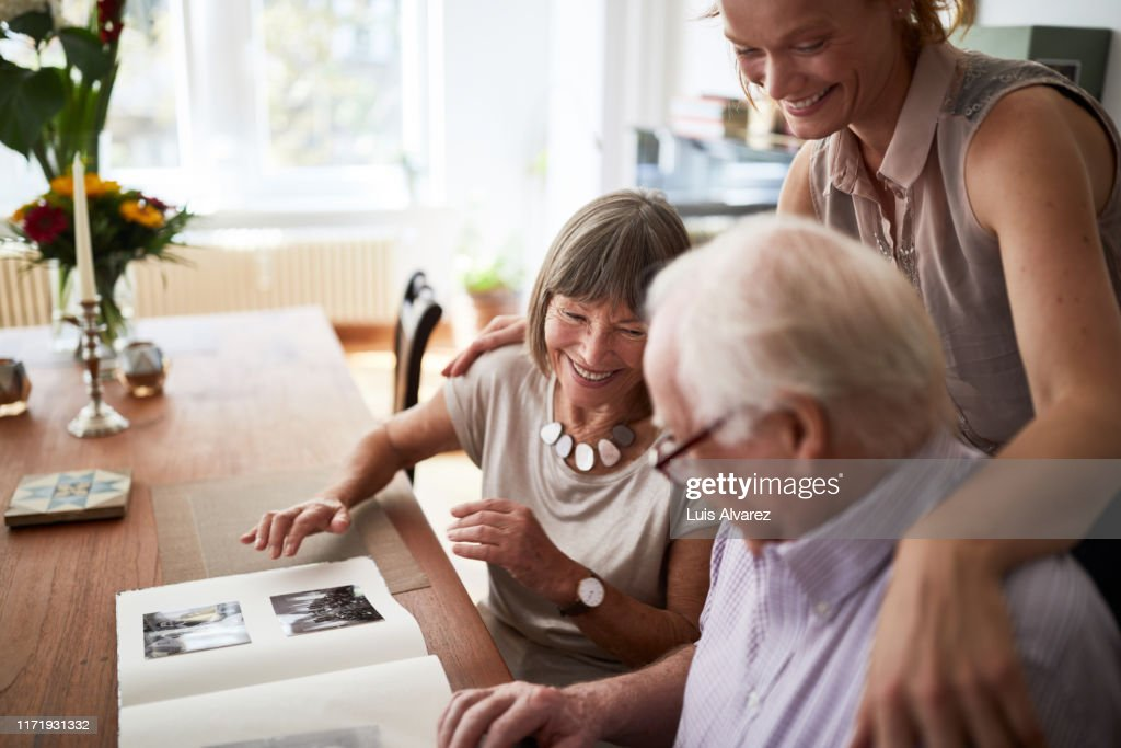 Family looking at photos in album : Stock Photo