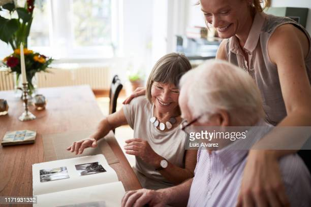 family looking at photos in album - daughter photos stock pictures, royalty-free photos & images