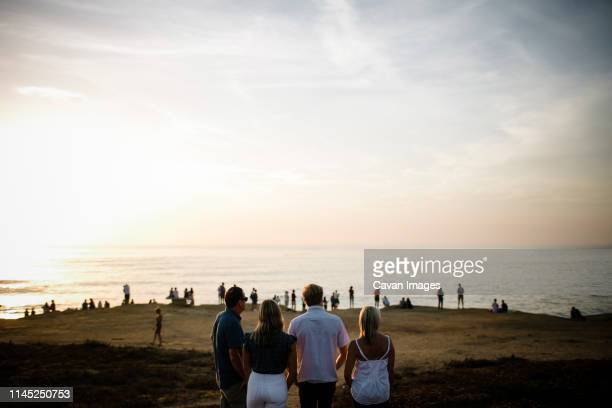 family looking at sea while standing on cliff against sky during sunset - four people stock pictures, royalty-free photos & images