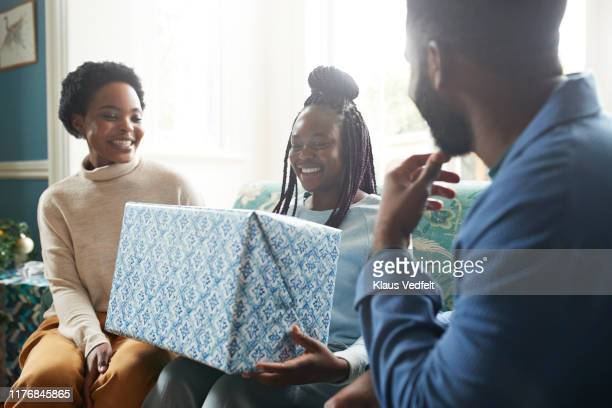 family looking at teenage girl holding gift box - birthday gift stock pictures, royalty-free photos & images