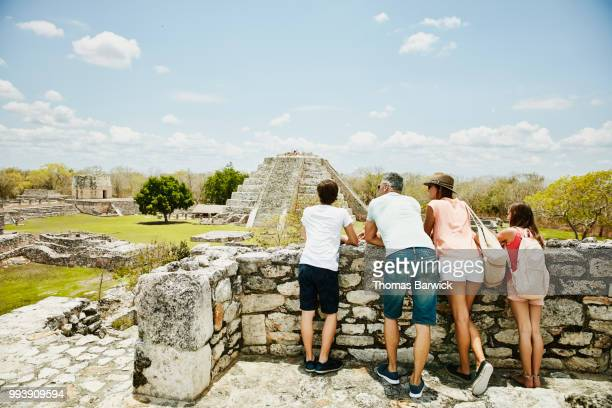 family looking at view while exploring mayapan ruins during vacation - cultura maya fotografías e imágenes de stock