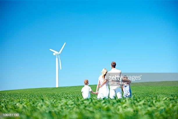 family looking at wind turbine - onschuld stockfoto's en -beelden