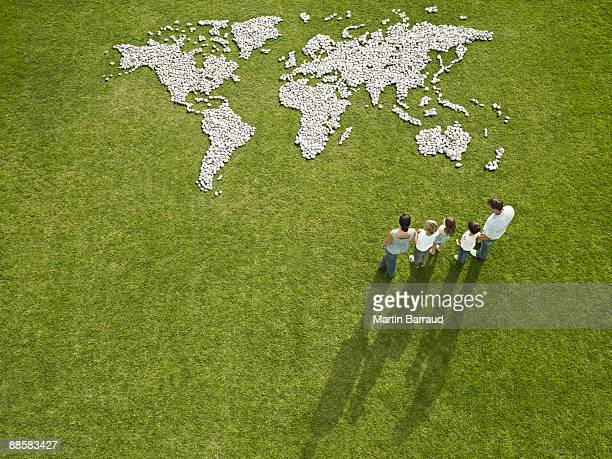 Family looking at world map made of rocks