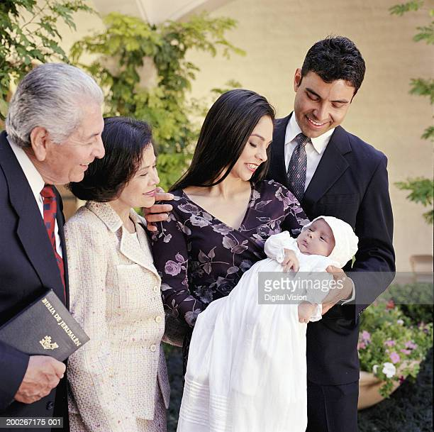 Family looking down at baby boy (0-3 months) in christening gown