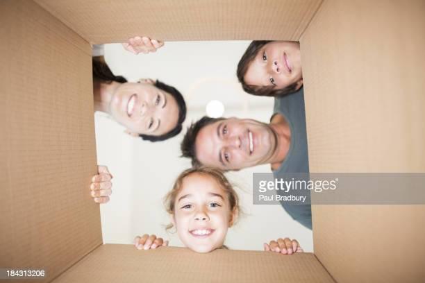 Family looking down at camera through cardboard box